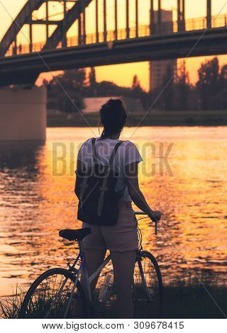 Cycling In Sunset. Lifestyle Concept. Hipster Woman Cycling In Sunset In City. Healthy Lifestyle. Pe