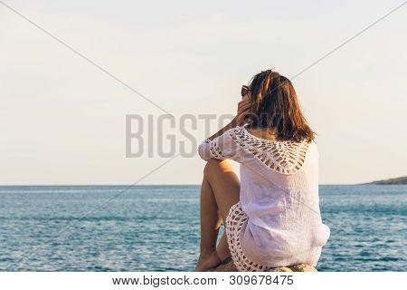 Traveler Girl Relaxing On Beach. Young Girl Traveler Relaxing In Vacation. Traveler Relaxing On Rock