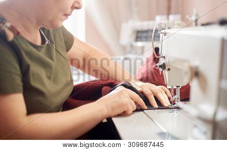 Woman Clothier Sitting At Workplace In Atelier Stitching Red Skirt With Professional Sewing Machine.
