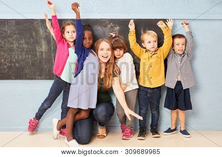 Cheering children and teacher together at the blackboard of a preschool or elementary school
