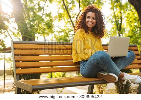 Photo of a pleased cheerful young beautiful curly student girl sitting outdoors in nature park using laptop computer.