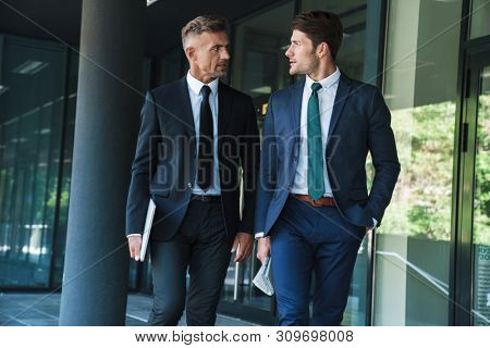Portrait of two serious businessmen partners dressed in formal suit walking and having conversation outside job center during working meeting