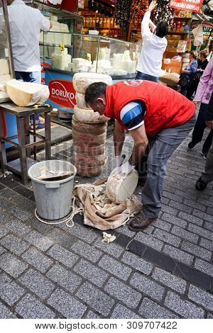 Cheesemaker Prepares His Wares For Sale At The Outdoor Food Market In Istanbul