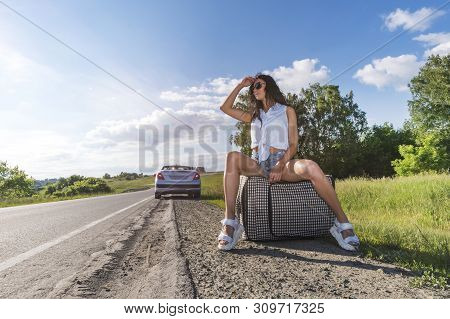 Young Woman Hitch-hiking On A Road With Luggage Bag At Fields. Girl Is Sitting On Baggage And Waitin