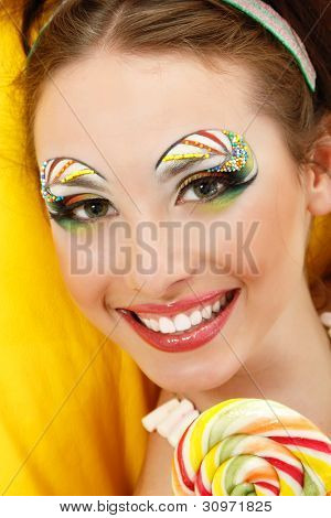 portrait of young smiling woman with beautiful make-up holding sweet candy isolated on white background
