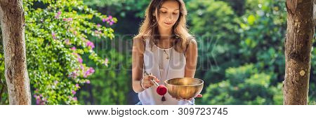 Woman Playing On Tibetan Singing Bowl While Sitting On Yoga Mat Against A Waterfall. Vintage Tonned.