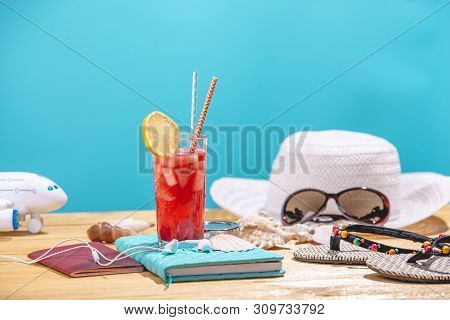 Glass Of Red Lemonade Drink With Lemon And Fruit And Straw On The Table. Concept Of Summer Sunny Vac