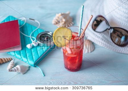 Glass Of Red Lemonade Drink With Lemon And Fruit And Straw On The Table. Bright Summer Sunny Holiday