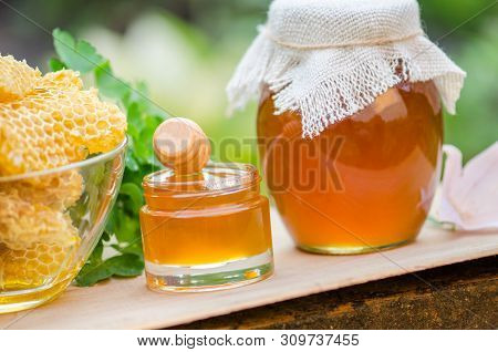 Honey Pot, Dipper, Jar Of Fresh Honey, Honeycomb On A Wooden Table Outdoors. Honey With Honey Dipper