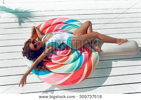 Slim Girl Having Fun On Colorful Inflatable Lollipop Pool Float. Bikini Model In Bright Swimwear Sun