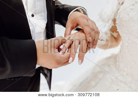 Groom Putting Jewelry Golden Ring On Bride Finger. Fine Art Rustic Wedding Ceremony. Love And Marria