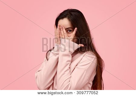 Timid Teen Girl With Long Hair Covering Face With Hand And Peeking Through Fingers Against Pink Back