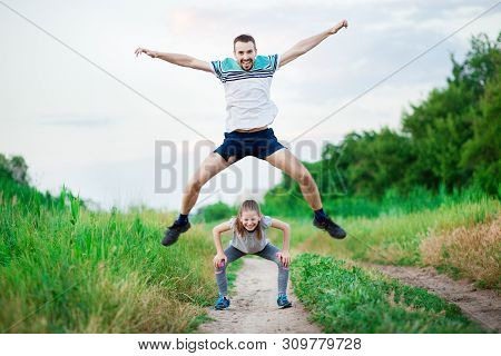 Sport Family Portrait Of Handsome Father And His Cute Little Daughter Play Leap Frog Outdoor At Suns