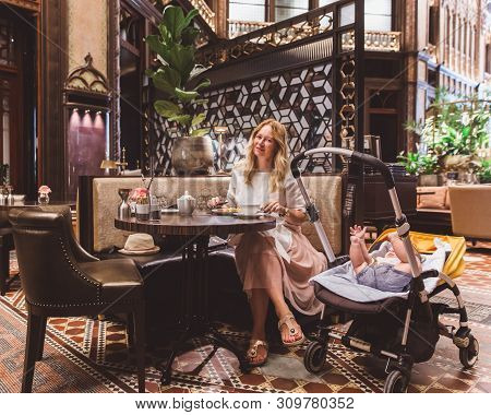 Beautiful Woman In A White Dress With Her Son Has A Rest In The Cafe In Parisi Udvar Hotel In V Dist