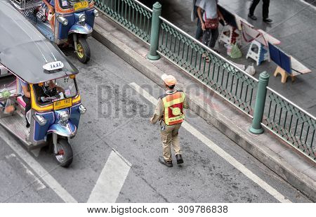 Bangkok, Thailand - June 29: Unnamed Traffic Warder Clears Illegally Parked Tuktuk Taxi In Bangkok O