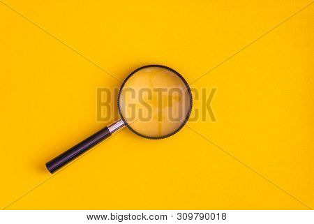 Magnifier Lies On Yellow And Blue Background. View From Above. Flat Lay. Copy Space.