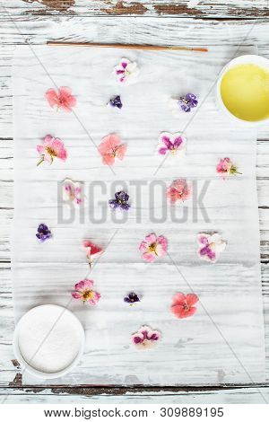 Ingredients For Making Homemade Sugared Or Crystallized Edible Flowers On A White Wooden Rustic Tabl