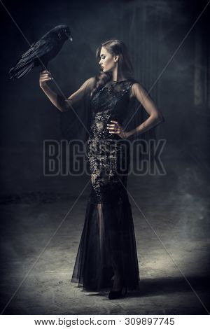 A beautiful brunette lady with a raven in ruins. Evening dress. Fashion, beauty.