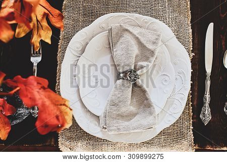 Thanksgiving Day Or Autumn Place Setting With Napkins And Cutlery On Burlap Table Runner Over A Rust