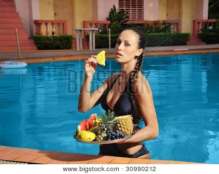 Young Beautiful Woman In The Pool With Fruit