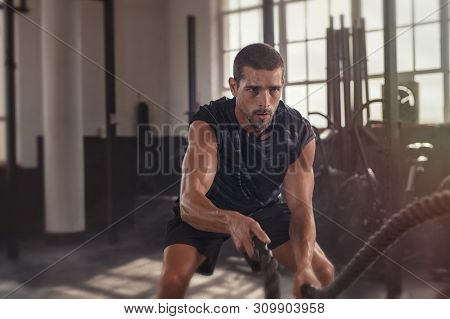 Athletic young man doing some fitness exercises with a rope. Determined fit guy doing battle ropes exercise at the grunge gym. Handsome man training with effort.