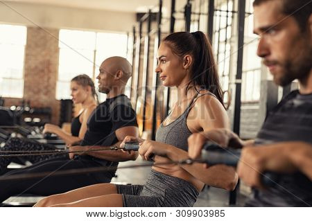 Group of people exercising in gym using rowing machine together. Side view of sportswoman doing exercise on rowing machine in center. Muscular girl and sporty men workout on training simulator at club