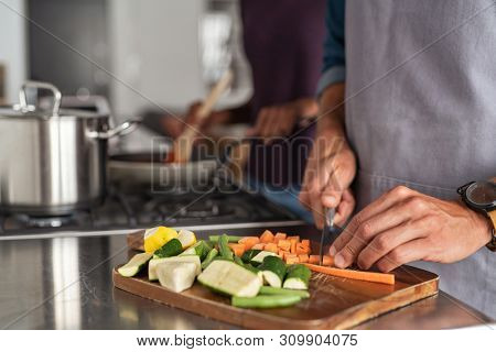 Closeup of hands slicing carrots on chopping board. Closeup of hands cutting vegetables in kitchen near the burners. Detail of man wearing apron chopping vegetables for a recipe at home.