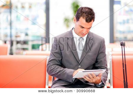 handsome businessman using tablet at airport