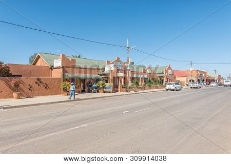 Warden, South Africa - May 1, 2019: A Street Scene With A Lodge, Restaurant, People And Vehicles, In