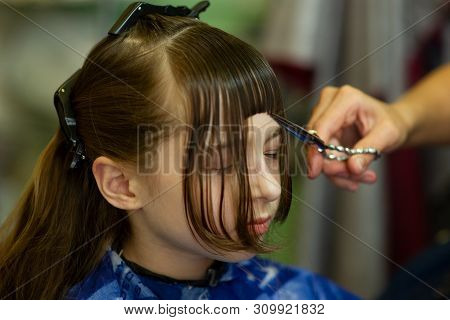 Hairdresser Making A Hair Style To Cute Little Girl. The Girl Cuts Off The Bangs. Work Hairdresser.