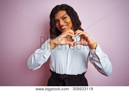 Beautiful transsexual transgender elegant businesswoman over isolated pink background smiling in love showing heart symbol and shape with hands. Romantic concept.