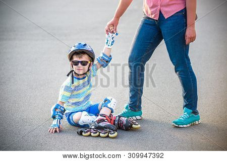 Preschooler Falls Over While Rollerblading With Mother In The Park. Little Boy Learning To Roller Sk
