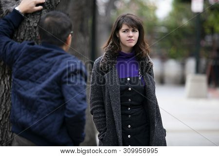 Man Being Rude, Leering And Cat Calling Or Sexually Harassing A Woman Walking On The Street.  Also D