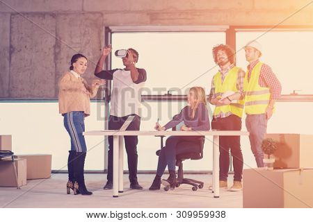 young multiethnic business team checking documents and business workflow on construction site using the virtual reality headset and laptop computer with sunlight through the windows during moving in a