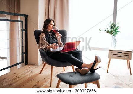 Young Businesswoman Work At Home. Drinking Red Wine From Glass And Look To Right. Hold Phone In Hand