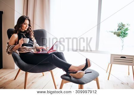 Young Businesswoman Work At Home. Drinking Coffe And Studying. Holding Feet On Small Stool. Typing O