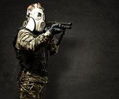 portrait of young soldier with gas mask aiming with shotgun against a grunge wall poster