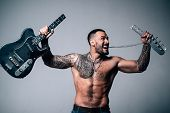 sexy abs of tattoo man broke guitar. rock concert. confidence charisma. sport fitness, health. brutal sportsman torso. anger. muscular macho man with athletic body. music. electro guitar player. poster