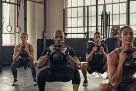 Fitness women and determined men exercising with kettlebell at gym. Group of young people doing a kettle bell exercise with squatting. Multiethnic group doing crouch exercise while holding weight.