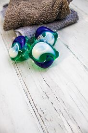 Laundry Day - Laundry Detergent Pods On A Laundry Folding Table With Washcloths.