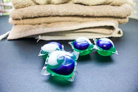 Laundry Day - Laundry Detergent Pods On A Laundry Folding Table With Tan Towels.