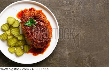 Close Up View Of Nashville Style Hot Chicken With Pickle On Plate Over Brown Background With Free Te