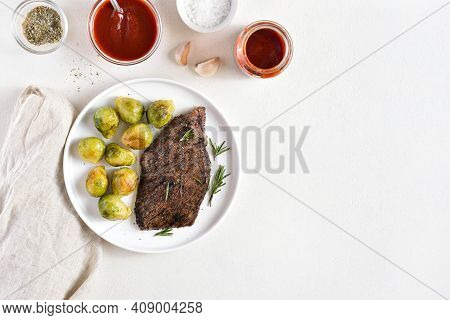 Grilled Beef Steak With Brussels Sprouts On Plate Over White Background With Free Text Space. Top Vi