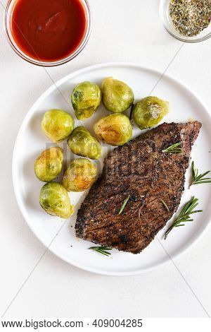 Grilled Beef Steak With Brussels Sprouts On Plate Over Light Background. Top View, Flat Lay
