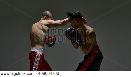 Fighting Guys During Mixed Fight Workout. Athletic Males In Boxing Gloves Training Martial Arts Tech