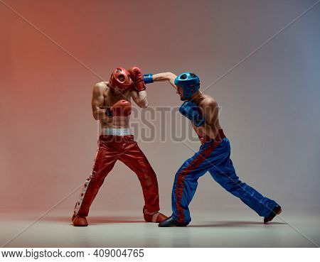 Sparring Of Fighting Males In Boxing Gloves And Helmets During Battle In Red Studio Light, Martial A