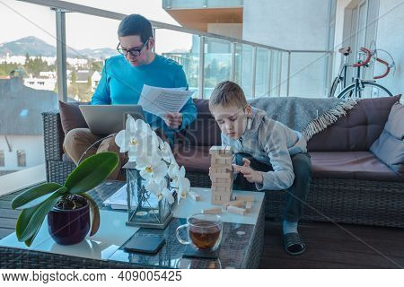 Stay and work at home dad. Father and son spend free time on terrace. Man working, child boy playing, builds, creating, wooden game toy. Weekend Family. Bonding concept.