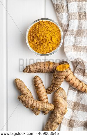 Indian turmeric powder and root. Turmeric spice. Ground turmeric in bowl. Top view.