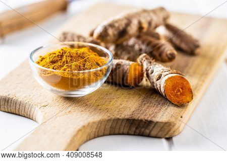 Indian turmeric powder and root. Turmeric spice. Ground turmeric in bowl.
