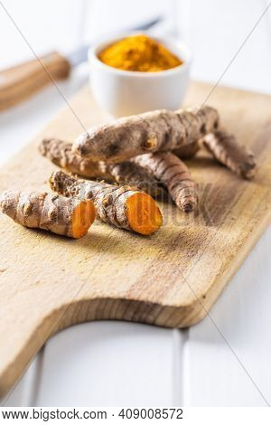 Indian turmeric root and powder. Turmeric spice on cutting board.